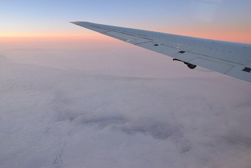 Sunset over the Southern Ocean between New Zealand and Antarctica. Pack ice is visible below the cloud layer.